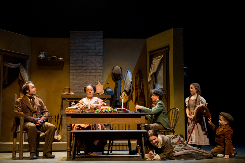 The Cratchit Family sitting around their table, Martha hiding (Cast of A Christmas Carol, Royal MTC) Photo by Dylan Hewlett Set design by Gillian Gallow, Costume design by Judith Bowden, Lighting design by Scott Henderson