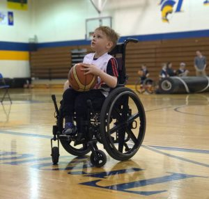 Isaac Vint sizes up his shot: sitting in his wheelchair, holding a basketball,