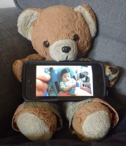 An old brown and beige teddy bear, holding an iPhone, on which is a picture of fingers holding a picture of a dark haired boy in a blue chair playing with a toy sitting on a red table.